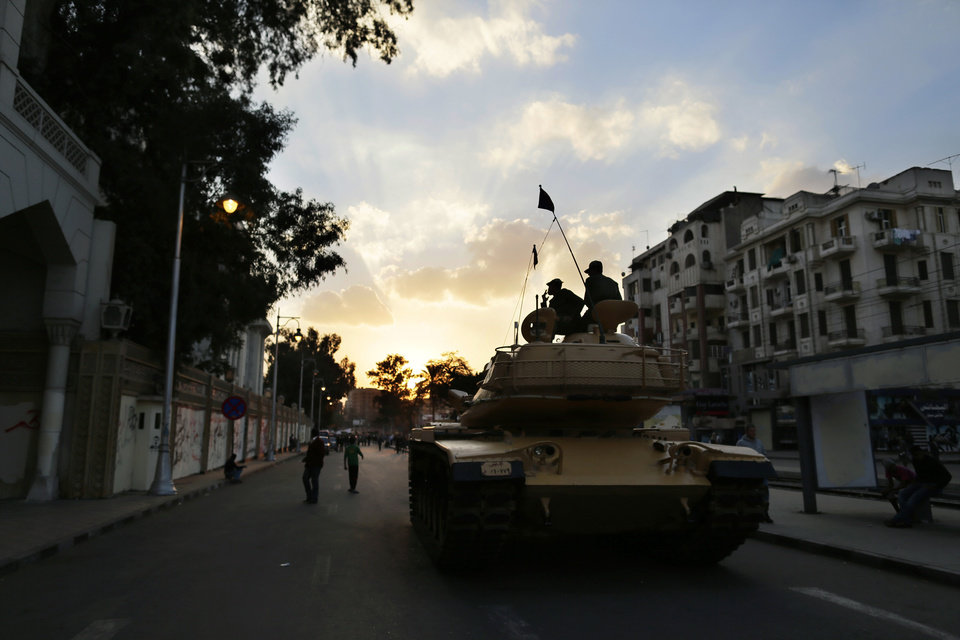 Egyptian army soldiers set on top of their tank as the sun set outside the presidential palace, background, in Cairo, Egypt, Saturday, Dec. 8, 2012. Egypt's military has warned of 'disastrous consequences' if the political crisis gripping the country is not resolved through dialogue. (AP Photo/Hassan Ammar)