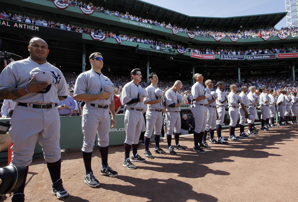 Photo -   New York Yankees players stand for the national anthem in throw-back uniforms prior to a baseball game against the Boston Red Sox at Fenway Park in Boston, Friday, April 20, 2012, during a celebration of the 100th anniversary of the first regular-season game at the ball park. (AP Photo/Elise Amendola)