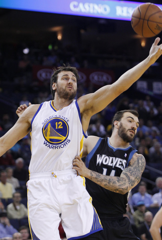 Photo - Golden State Warriors' Andrew Bogut reaches for a rebound in front of Minnesota Timberwolves' Jose Barea during the first half of an NBA basketball game, Tuesday, April 9, 2013, in Oakland, Calif. (AP Photo/George Nikitin)