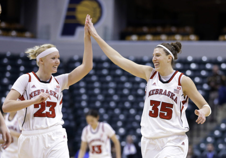 Photo - Nebraska's Emily Cady, left, and Jordan Hoope celebrate in the second half of an NCAA college basketball game against Iowa in the finals of the Big Ten women's tournament in Indianapolis, Sunday, March 9, 2014. Nebraska won 72-65. (AP Photo/Michael Conroy)