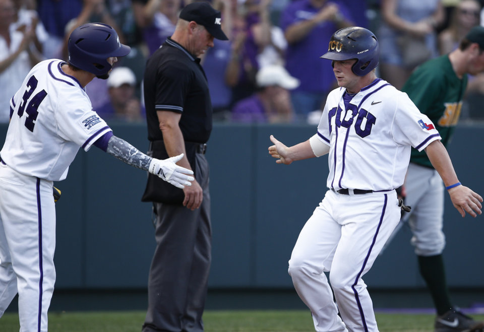 Photo - TCU's Boomer White, right, is congratulated by teammate Garrett Crain, left, after scoring a run on a single hit by Kevin Cron against Siena during the first inning of an NCAA college baseball regional tournament game in Fort Worth, Texas, Friday, May 30, 2014. (AP Photo/Jim Cowsert)