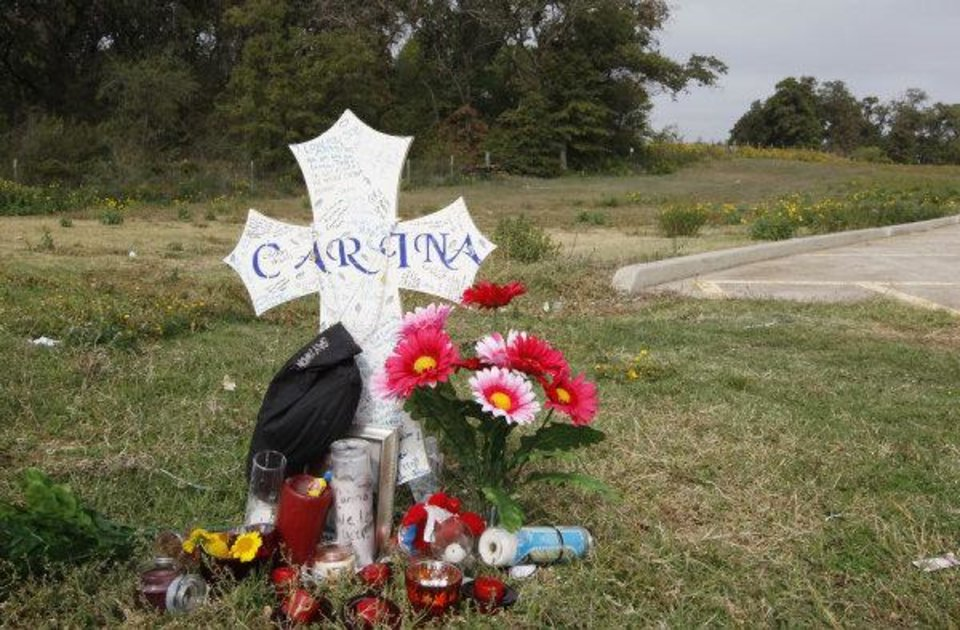 A memorial to Carina Saunders sits behind a grocery store in Bethany near the wooded area where her dismembered body was found stuffed in a duffel bag.  (AP Photo/Sue Ogrocki) ORG XMIT: OKSO102 <strong>Sue Ogrocki - AP</strong>