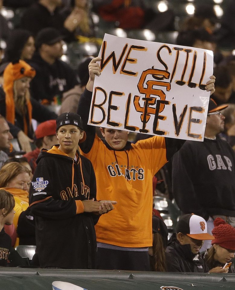 Photo - A pair of San Francisco Giants fans hold up a sign in left field during the ninth inning of their baseball game against the New York Mets Tuesday, July 9, 2013, in San Francisco. New York won the game 10-6. (AP Photo/Eric Risberg)
