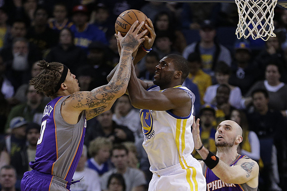Photo - Phoenix Suns' Michael Beasley, left, and Golden State Warriors' Festus Ezeli fight for the ball in the first half of an NBA basketball game Saturday, Feb. 2, 2013, in Oakland, Calif. (AP Photo/Ben Margot)