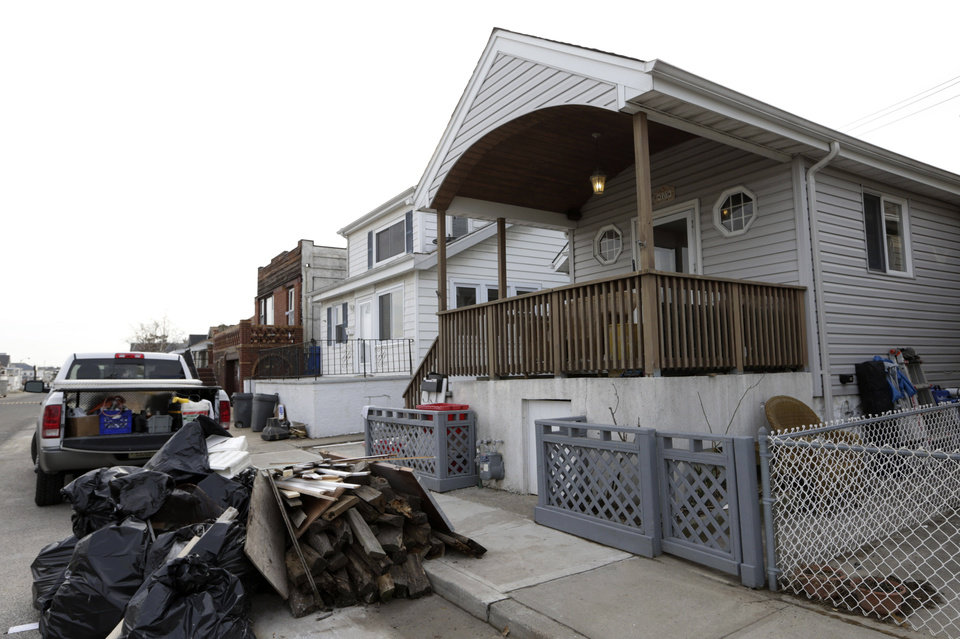 Photo - Trash is piled up outside the Troy family home in Long Beach, N.Y., Wednesday, Dec. 12, 2012, as workers redo the interior after Superstorm Sandy's surge did serious damage there. Donald Denihan, who endured three near-death experiences, is paying for repairs while the Troy family stays in nearby Point Lookout, at the second house of another generous family. (AP Photo/Kathy Willens)