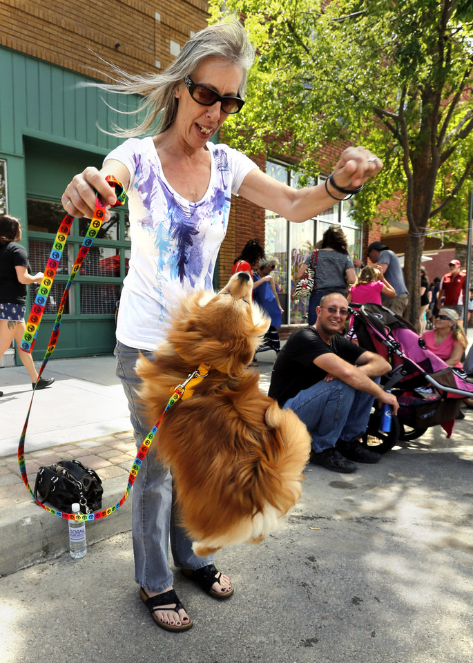 Photo - Angela Bauknecht with Groovy Paws Animal Rescue, dances with rescue dog Fox during the Norman Music Festival on Saturday, April 26, 2014 in Norman, Okla.  Photo by Steve Sisney, The Oklahoman