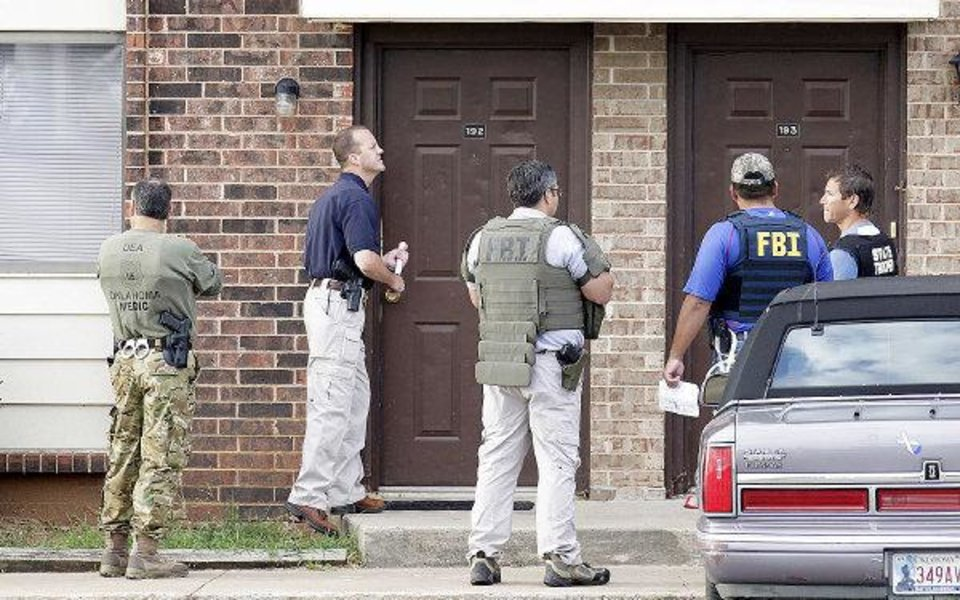 Agents with the Edmond Police Department, the FBI and the Oklahoma Highway Patrol execute search warrants Wednesday morning at Rolling Green Apartments in Edmond. PHOTO BY PAUL B. SOUTHERLAND, THE OKLAHOMAN <strong>PAUL B. SOUTHERLAND</strong>