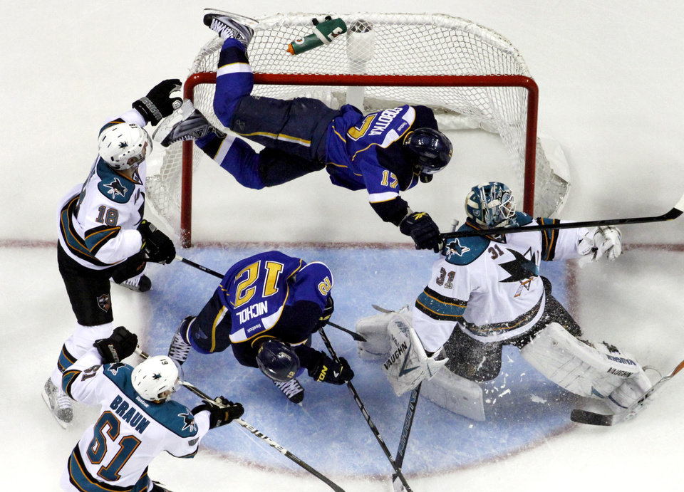 Photo -   St. Louis Blues' Vladimir Sobotka, top, of the Czech Republic, goes flying into the goal over San Jose Sharks goalie Antti Niemi, right, of Finland, and Blues' Scott Nichol (12) as Sharks' Dominic Moore (18) and Justin Braun (61) watch during the second period in Game 2 of an NHL Stanley Cup first-round hockey playoff series Saturday, April 14, 2012, in St. Louis. (AP Photo/Jeff Roberson)
