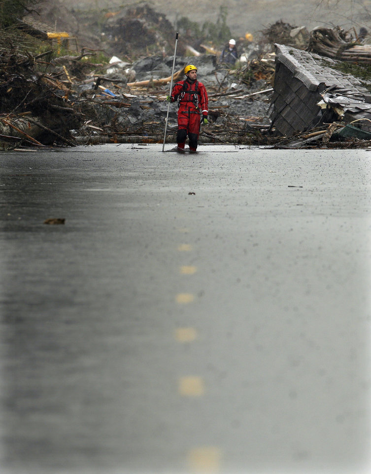 Photo - A search and rescue worker carrying a probe wades through water covering Washington Highway 530 Thursday, March 27, 2014, on the eastern edge of the massive mudslide that struck Saturday near Darrington, Wash. (AP Photo/Ted S. Warren, Pool)