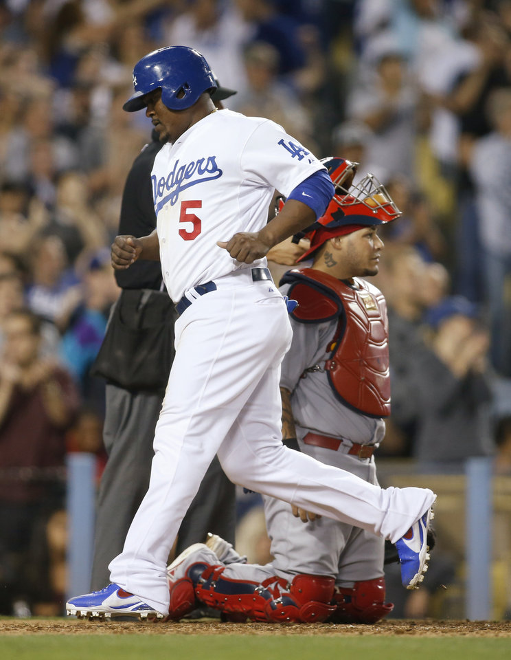 Photo - Los Angeles Dodgers' Juan Uribe scores next to St. Louis Cardinals catcher Yadier Molina on a single by Justin Turner during the eighth inning of a baseball game, Thursday, June 26, 2014, in Los Angeles. The Dodgers won 1-0. (AP Photo/Danny Moloshok)