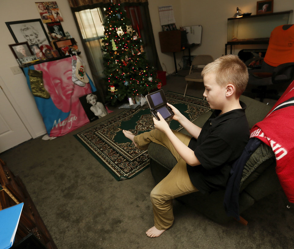 Photo - Jesse Redwine, 9, plays a video game in the living room of his family's Central Oklahoma Habitat for Humanity home on Durland Way.  NATE BILLINGS - The Oklahoman