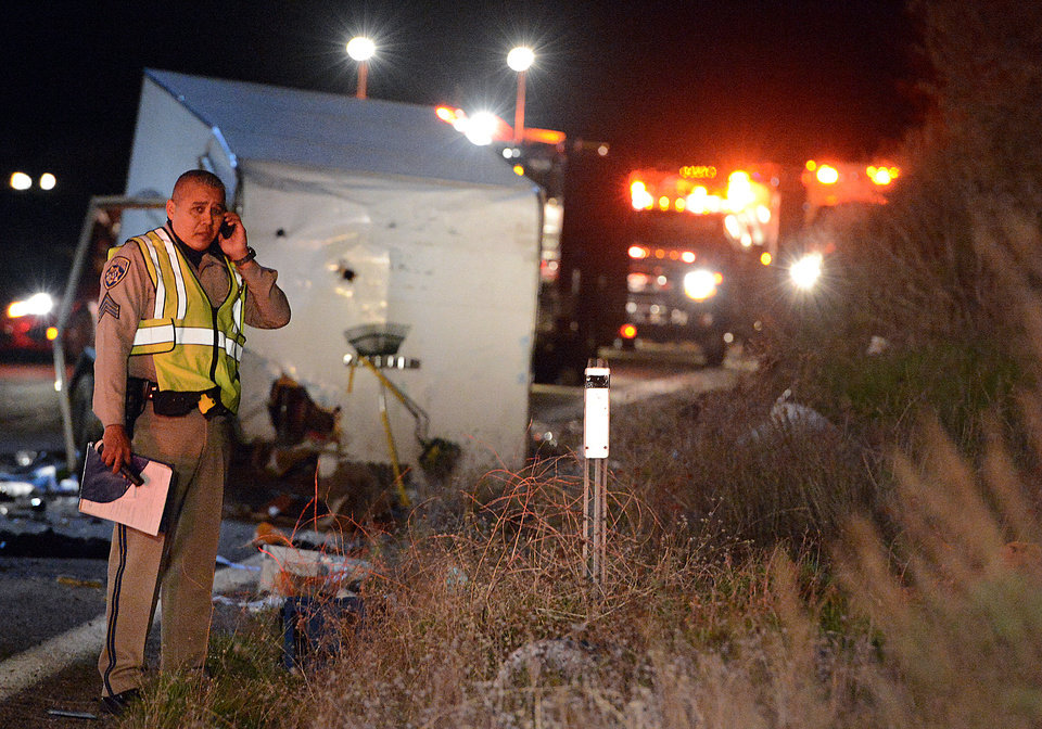 Photo - A California Highway Patrol officer stands near the crash scene where at least eight people were killed and nearly two dozen were injured when a bus carrying a group from Tijuana, Mexico crashed with two other vehicles on its way back from Big Bear Lake on Highway 38 north of Yucaipa, Calif., Sunday, Feb. 3, 2013. Both sides of the highway remained closed two and a half hours after the crash and it was unclear when it would reopen. (AP Photo/The Sun, Rick Sforza) MANDATORY CREDIT