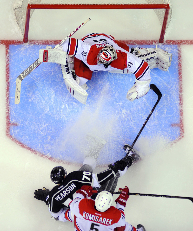 Photo - Los Angeles Kings left wing Tanner Pearson, center, tries to get a shot in on Carolina Hurricanes goalie Anton Khudobin, top, of Kazakhstan, as Mike Komisarek defends during the first period of an NHL hockey game, Saturday, March 1, 2014, in Los Angeles. (AP Photo/Mark J. Terrill)