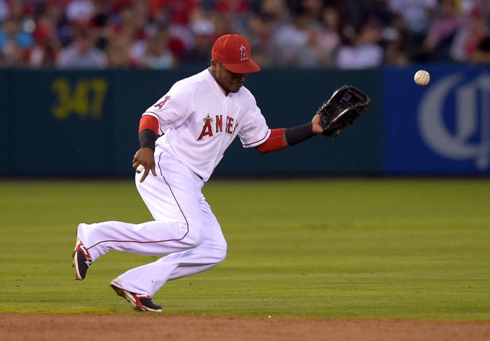 Photo - Los Angeles Angels shortstop Erick Aybar can't handle a ball hit for a single by Philadelphia Phillies' Carlos Ruiz during the second inning of a baseball game, Wednesday, Aug. 13, 2014, in Anaheim, Calif. (AP Photo/Mark J. Terrill)
