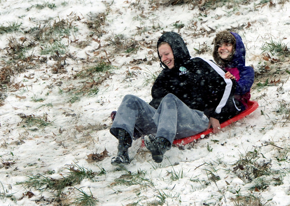 Photo - Former Owensboro Catholic High School basketball player Mary Kate Clemens, 19, left, and her younger sister, Sarah Beth Clemens, 11, enjoy the thrill of sledding down the big hill at Chautaqua Park in Owensboro, Ky., on Wednesday morning, Dec. 26, 2012. (AP Photo/The Messenger-Inquirer, Gary Emord-Netzley)