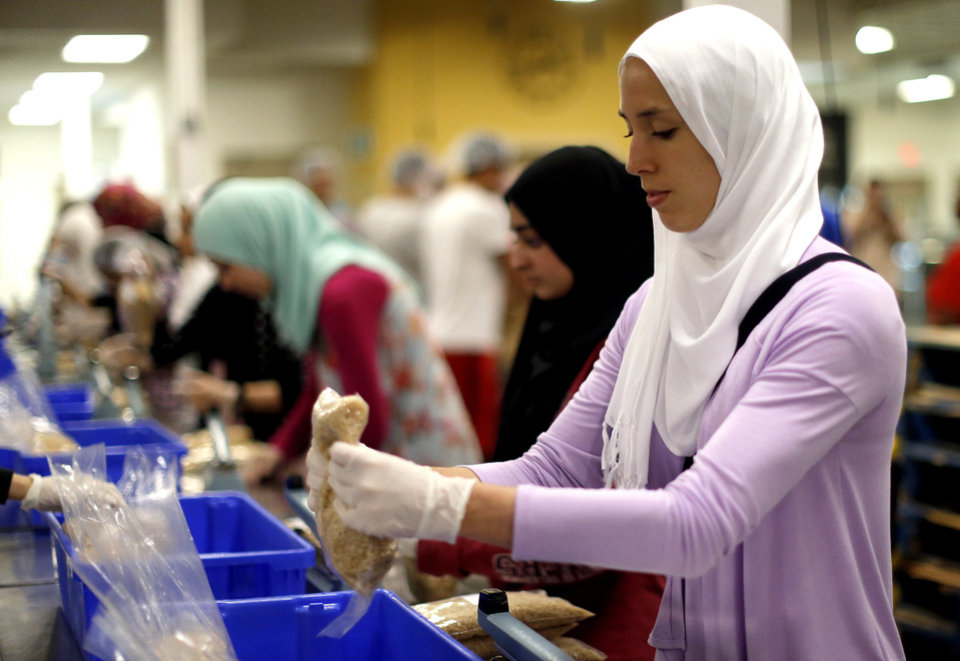 Photo - Jackie Mahjoub packages rice while volunteering during the fasting hours of Ramadan at the Regional Food Bank of Oklahoma, Saturday, July 27,  2013, in Oklahoma City. About 150 Muslims from various  organizations from across the state volunteered. Photo by Sarah Phipps, The Oklahoman