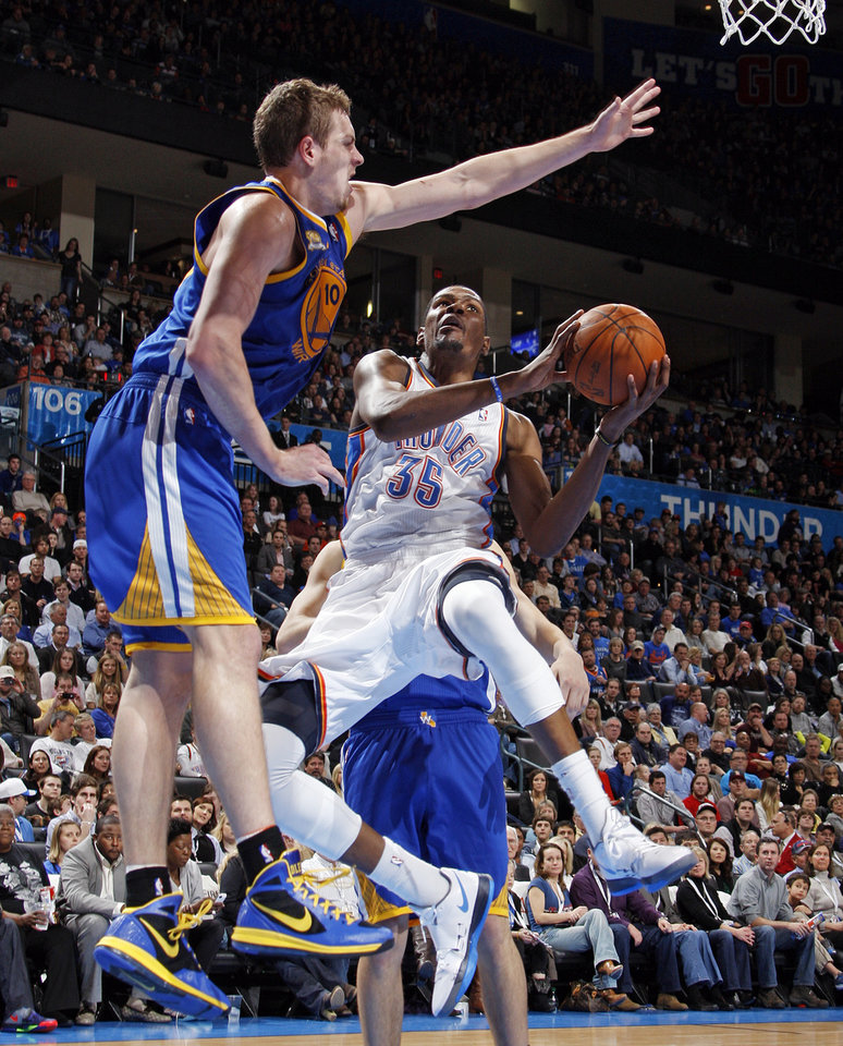 Photo - Oklahoma City's Kevin Durant (35) moves to the hoop as Golden State's David Lee (10) defends during the NBA basketball game between the Oklahoma City Thunder and the Golden State Warriors at the Chesapeake Energy Arena in Oklahoma City, Friday, Feb. 17, 2012. Photo by Nate Billings, The Oklahoman