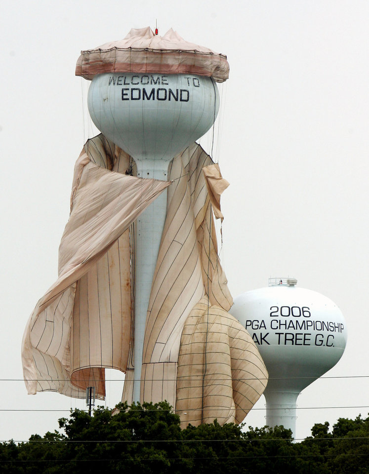 Workers try their best to get a containment shroud under control after high winds loosened the guy-lines around the water tower at I-35 and 2nd Street in Edmond, OK, Friday, May 8, 2009. BY PAUL HELLSTERN, THE OKLAHOMAN