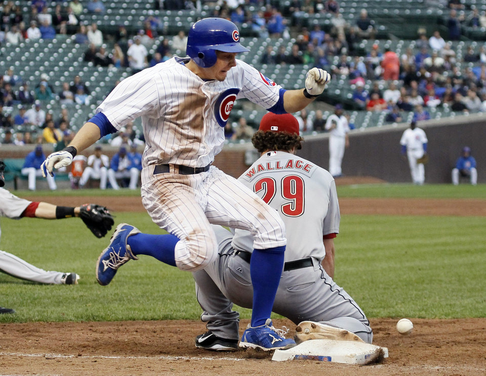 Chicago Cubs' Tony Campana, left, is safe at first after Houston Astros first baseman Brett Wallace is unable to field a throw from second baseman Tyler Greene during the ninth inning of a baseball game, Wednesday, Oct. 3 2012, in Chicago. The Cubs won 5-4. (AP Photo/Charles Rex Arbogast)
