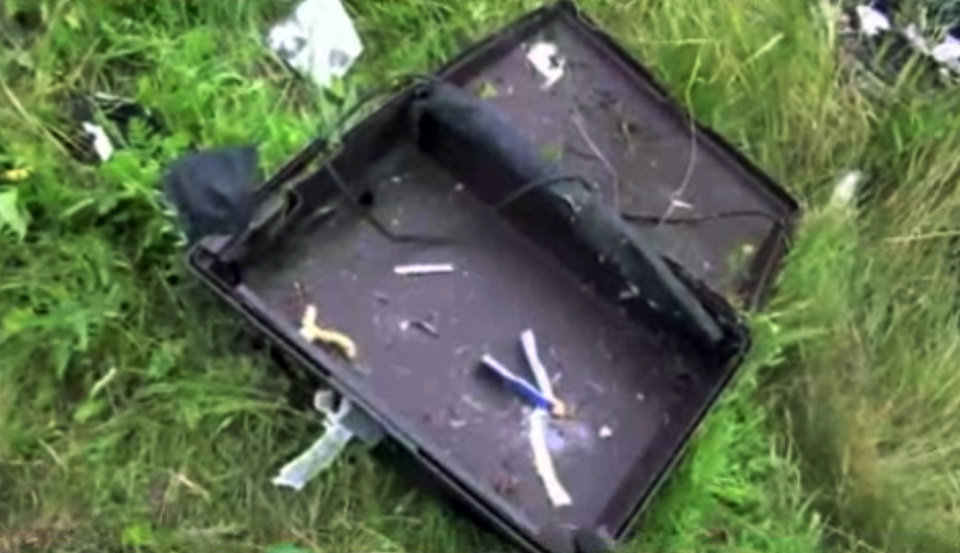 Photo - This image taken from video, Thursday July 17, 2014, shows a suitcase found in the wreckage of a passenger plane carrying 295 people after it was shot down Thursday as it flew over Ukraine, near the village of Hrabove, in eastern Ukraine. Malaysia Airlines tweeted that it lost contact with one of its flights as it was traveling from Amsterdam to Kuala Lumpur over Ukrainian airspace. (AP Photo/Channel 1) RUSSIA OUT - TV OUT