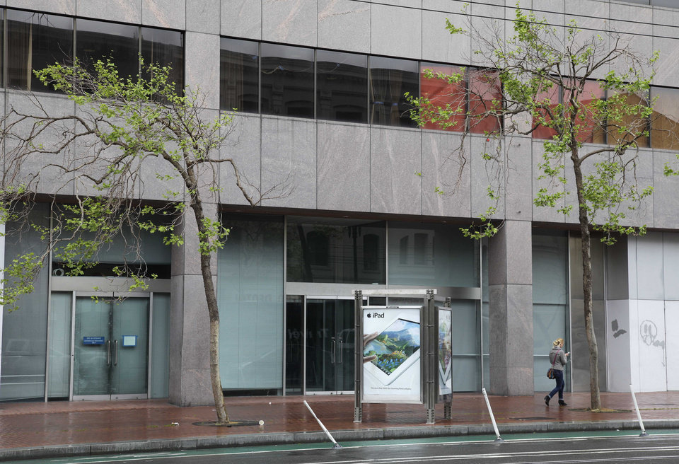 """Photo -   In this photo taken Thursday, May 3, 2012, a woman walks past a vacant office building on Market Street near Twitter's new headquarters in San Francisco. With Twitter's new headquarters set to open there soon, residents of a San Francisco neighborhood notorious for crime, drugs and homelessness remain among the least likely to have any way to send a tweet, much less access to basic goods and services. At a recent weekend """"hackathon,"""" engineers and entrepreneurs sought ways to use tech to help people in the Tenderloin and Mid-Market Street area find food, housing, healthcare and jobs. In the process, city leaders hope to ease tensions between needy locals and newly arriving startups flush with cash. (AP Photo/Eric Risberg)"""