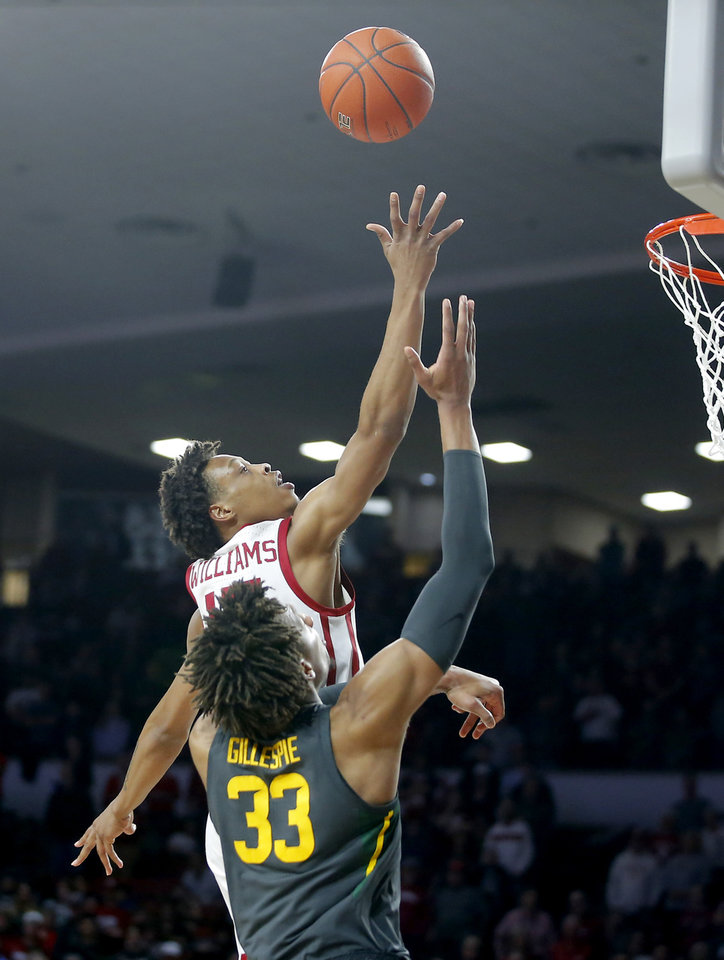 Photo - Oklahoma's Kristian Doolittle (21) puts up a shot beside Baylor's Freddie Gillespie (33) during a men's NCAA basketball game between the University of Oklahoma Sooners (OU) and the Baylor Bears at the Lloyd Noble Center in Norman, Okla., Tuesday, Feb. 18, 2020. Baylor won 65-54. [Bryan Terry/The Oklahoman]