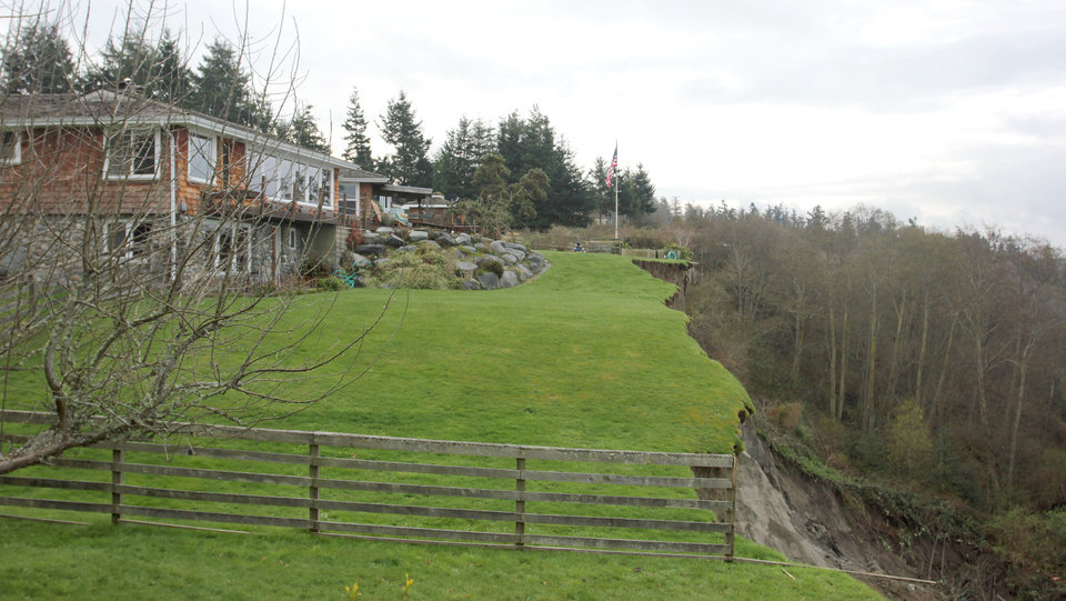 This Thursday, March 28, 2013 photo shows a home that lost a significant portion of its lawn in Wednesday's massive landslide near Coupeville, Wash. Authorities spent the day assessing the damage and danger to homes remaining near the slide as nervous residents waited for more detailed information about how safe the area is. (AP Photo/Manuel Valdes)
