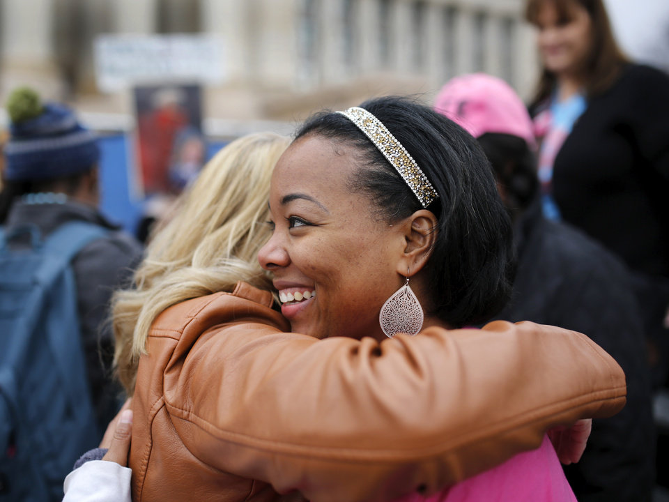 Photo - Tamya Cox, right, is hugged by a woman in the crowd after Cox's speech. Cox is with Planned Parenthood Great Plains in Oklahoma. A crowd estimated by organizers to be as many as 7,000 people came to the state Capitol in Oklahoma City Saturday, Jan. 21, 2017, to rally, using their voices and signs to express displeasure with the nation's new administration as part of a larger network of marches taking place across the country following Donald Trump's inauguration.   The Women's March on Oklahoma included a walk along Lincoln Blvd., with the Capitol as a backdrop, and a rally on the Capitol's south plaza that featured nearly a dozen speakers.  Photo by Jim Beckel, The Oklahoman