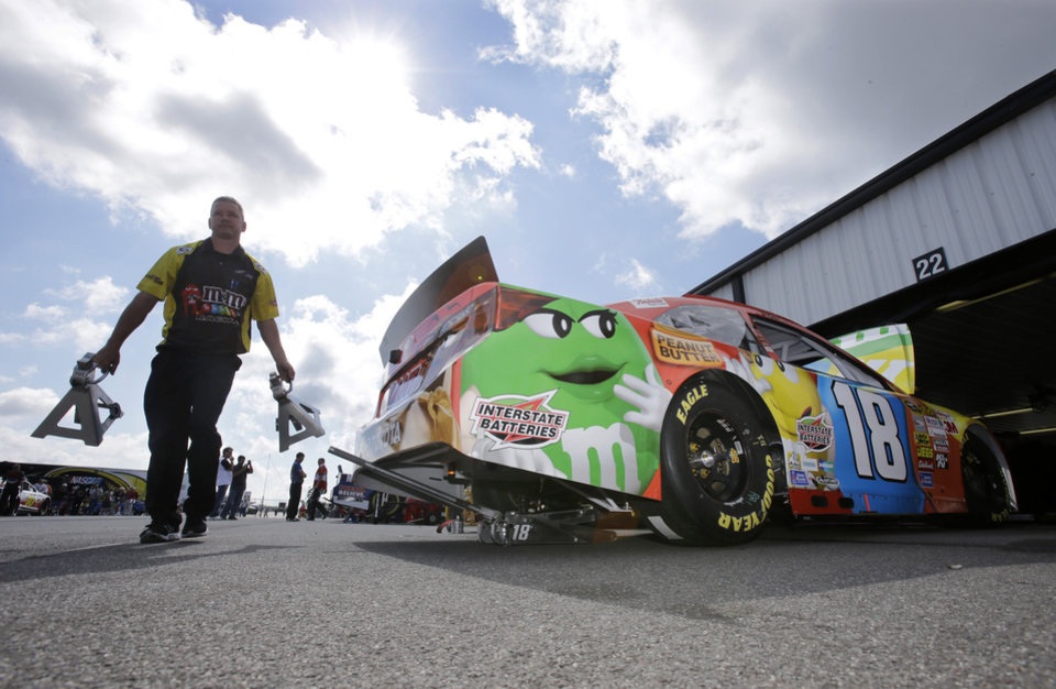Photo - Crew member Marc Browining carries jack stands near the race car of Kyle Busch in the garage area during practice Friday Aug. 2, 2013, for Sunday's NASCAR Sprint Cup Series auto race in Long Pond, Pa. (AP Photo/Mel Evans)