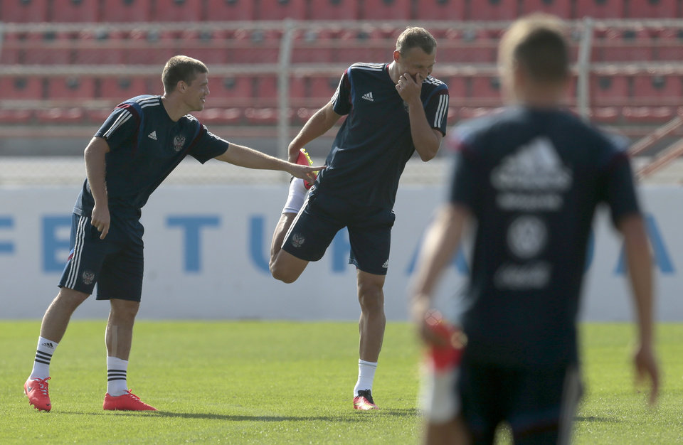 Photo - Igor Denisov, left, and Vasily Berezutsky share a joke during the training session of Russian national soccer team in Itu, Brazil, on Sunday, June 15, 2014. Russia will play in group H of the 2014 soccer World Cup. (AP Photo/Ivan Sekretarev)