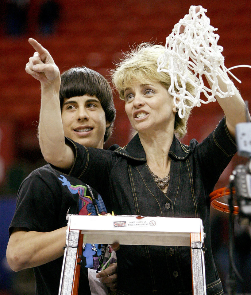 Photo - Baylor coach Kim Mulkey cuts down the net with her son Kramer after winning the championship game of the Big 12 Women's Basketball Championship between Baylor and Texas A&M at the Cox center in Oklahoma City, Sunday, March 15, 2009. PHOTO BY BRYAN TERRY, THE OKLAHOMAN