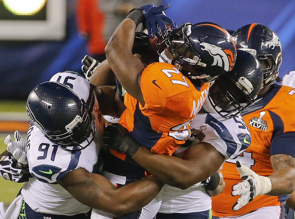 Photo - Denver Broncos running back Knowshon Moreno (27) is tackled by Seattle Seahawks defensive end Chris Clemons (91) and defensive end Cliff Avril (56) during the first half of the NFL Super Bowl XLVIII football game Sunday, Feb. 2, 2014, in East Rutherford, N.J. (AP Photo/Matt York)