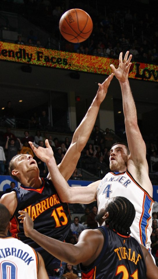 Photo - Oklahoma City's Nick Collison shoots over the defense of Andris Biedrins of Golden State in the second half during the NBA basketball game between the Golden State Warriors and the Oklahoma City Thunder at the Ford Center in Oklahoma City, Monday, December 8, 2008. Golden State won, 112-102.  BY NATE BILLINGS, THE OKLAHOMAN