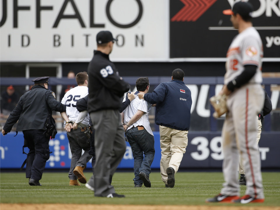 Photo - Baltimore Orioles second baseman Stephen Lombardozzi (12) watches as police and security officers escort two fans away after the fans interrupted play by running onto the field in the eighth inning of the Yankees 14-5 loss to the Orioles in a baseball game at Yankee Stadium in New York, Tuesday, April 8, 2014.  (AP Photo/Kathy Willens)