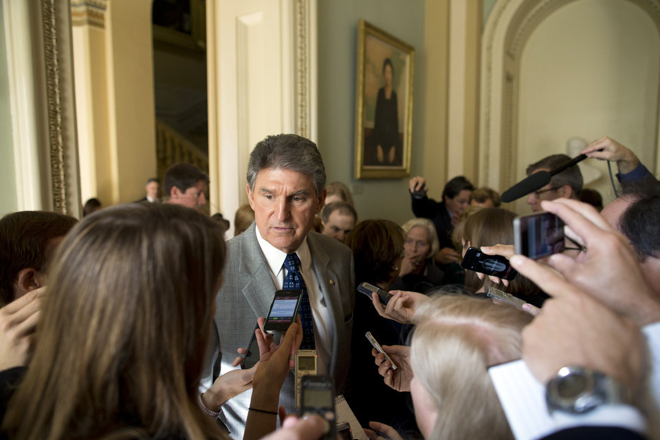 Photo - Sen. Joe Manchin, D-W.Va., talks with reporters on Capitol Hill on Monday, Oct. 14, 2013, in Washington. The Senate's top two leaders both expressed optimism Monday that they were closing in on an agreement to prevent a national financial default and reopen the government after a two-week partial shutdown. (AP Photo/ Evan Vucci)