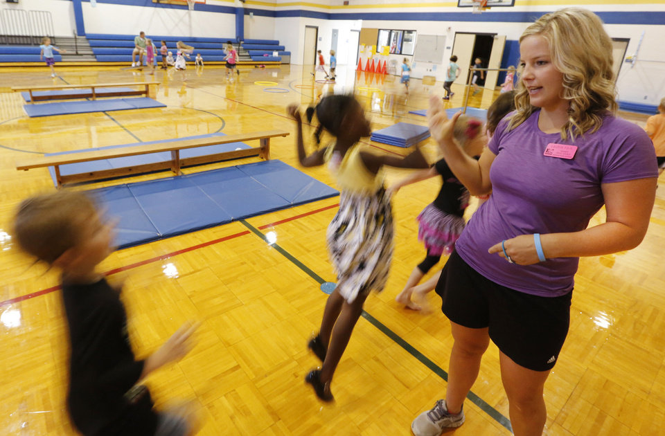 Photo - Orivis Risner Elementary physical education teacher Laurin Fain high-fives her students. Photo By Steve Gooch, The Oklahoman  Steve Gooch - The Oklahoman