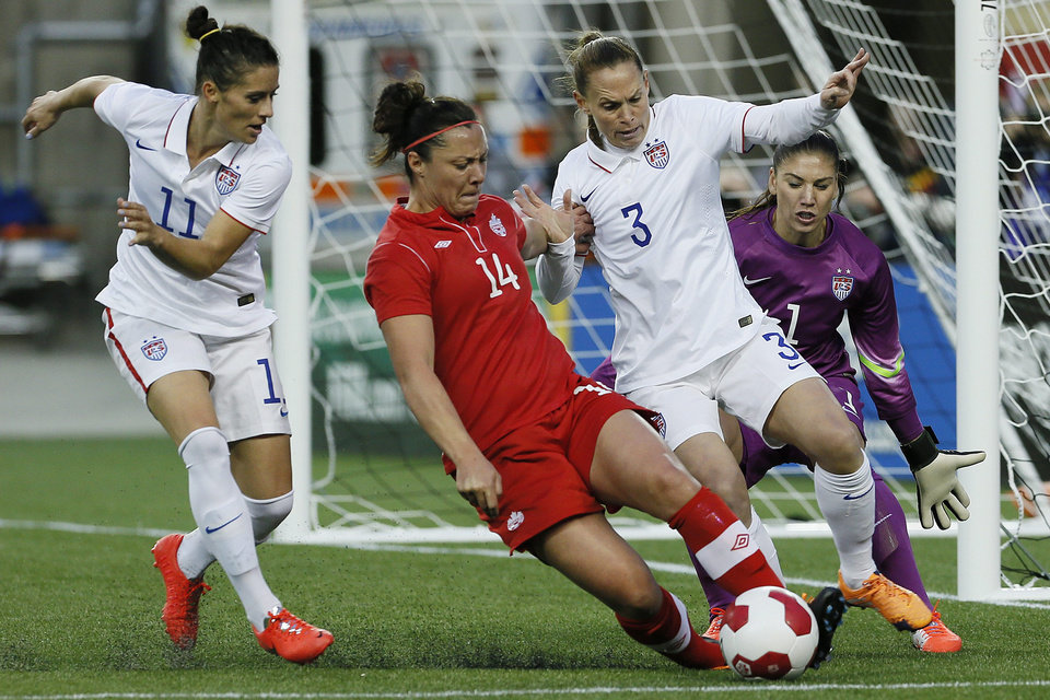 Photo - Canada's forward Melissa Tancredi (14) drives for the net as USA's goalkeeper Hope Solo (1) looks on as defenders Ali Krieger (11) and Christie Rampone (3) defend during the second half of an exhibition soccer match in Winnipeg, Manitoba, Thursday, May 8, 2014. (AP Photo/The Canadian Press, John Woods)