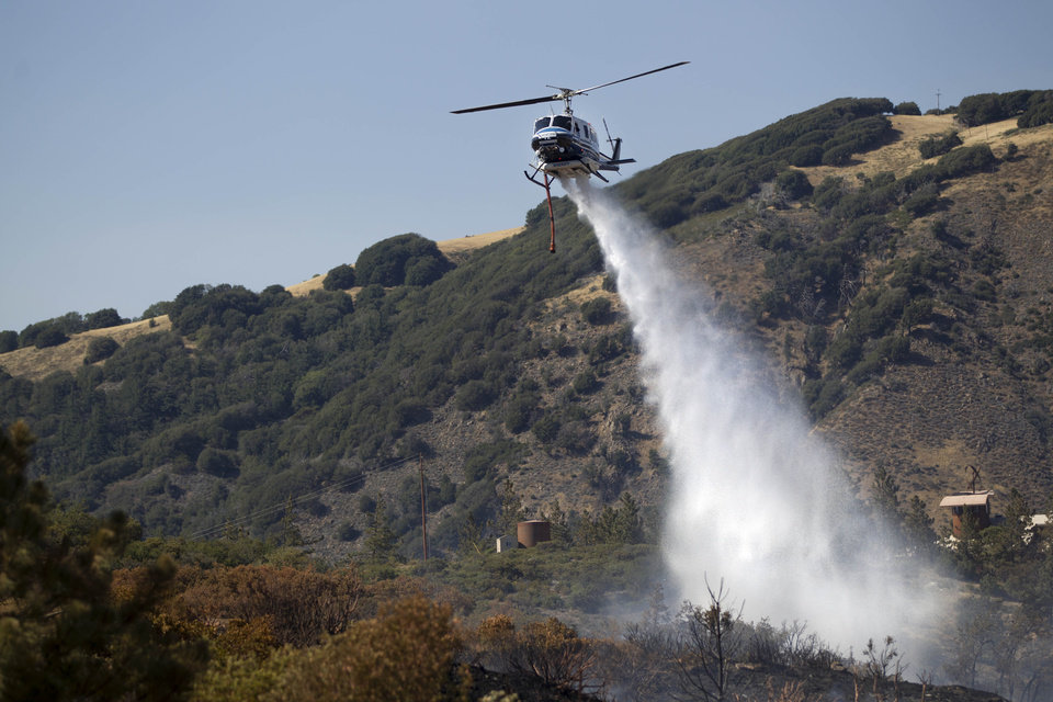 Photo - A firefighting helicopter drops a load of water on part of the Banner Fire in the mountain town of Julian, Calif., on Thursday, July 3, 2014. (AP Photo/UT San Diego, Sean M. Haffey) MANDATORY CREDIT