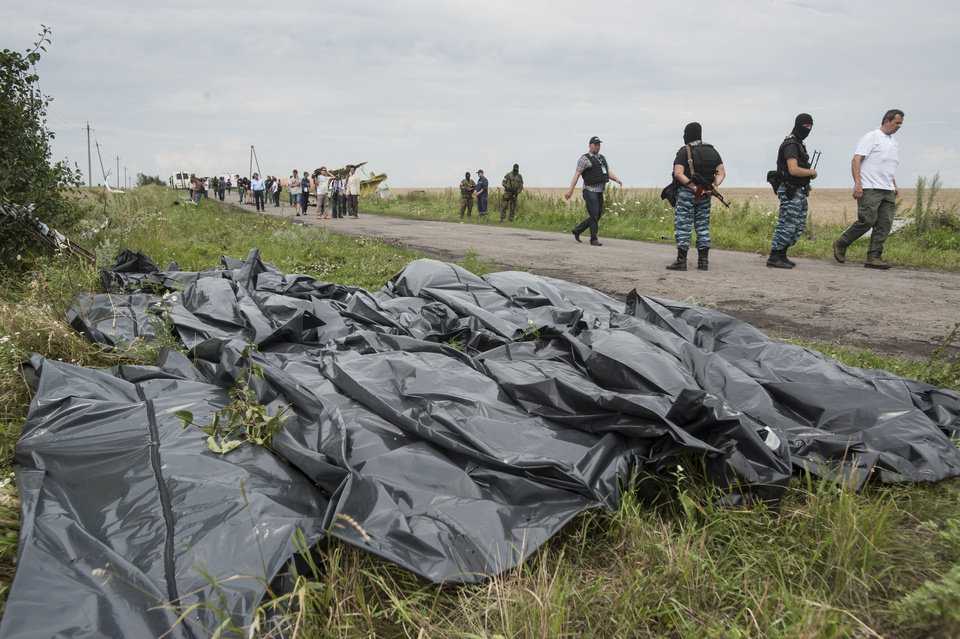 Photo - Pro-Russian fighters walk on a road with victims' bodies lying in bags by the side at the crash site of a Malaysia Airlines jet near the village of Hrabove, eastern Ukraine, Saturday, July 19, 2014. Ukraine accused Russia on Saturday of helping separatist rebels destroy evidence at the crash site of a Malaysia Airlines plane shot down in rebel-held territory — a charge the rebels denied. (AP Photo/Evgeniy Maloletka)