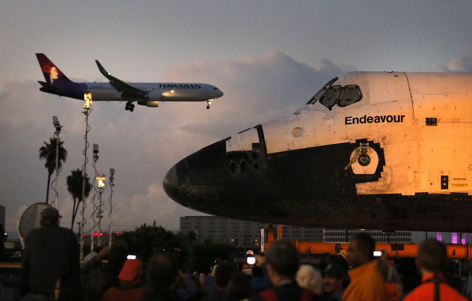 Photo -   The space shuttle Endeavour sits in a strip mall as a Hawaiian Airlines jet approaches a runway at Los Angeles International Airport in Los Angeles, Friday, Oct. 12, 2012. Endeavour's 12-mile road trip kicked off shortly before midnight Thursday as it moved from its hangar at the airport en route to the California Science Center, its ultimate destination. (AP Photo/Jae C. Hong)