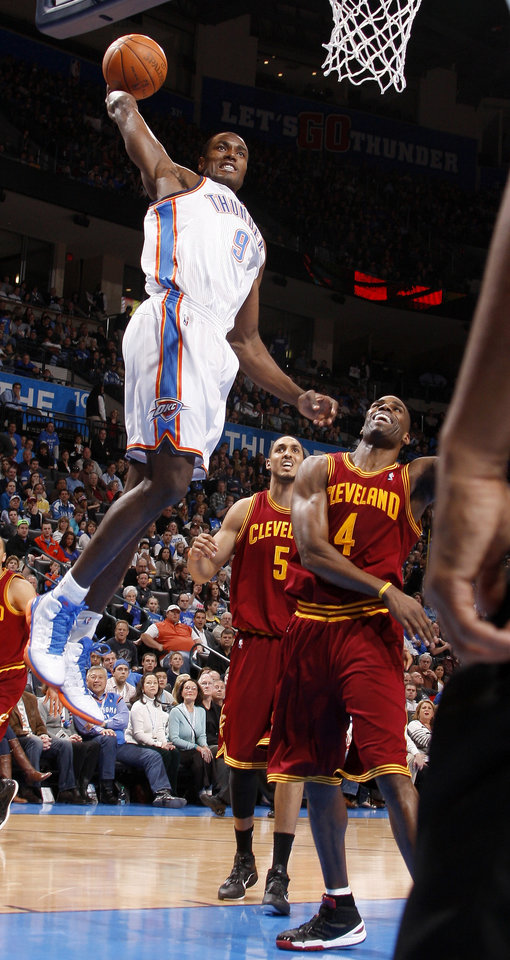 Photo - Oklahoma City's Serge Ibaka (9) goes up for a dunk beside Cleveland's Antawn Jamison (4), and Ryan Hollins (5) during the NBA basketball game between the Oklahoma City Thunder and the Cleveland Cavaliers at Chesapeake Energy Arena in Oklahoma City, Friday, March 9, 2012. Photo by Bryan Terry, The Oklahoman
