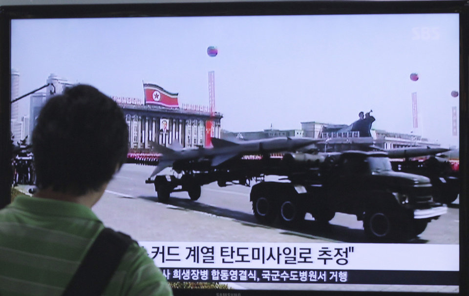 Photo - A man watches a TV news program showing file footage of a North Korean rocket carried during a military parade at Seoul Railway Station in Seoul, South Korea, Sunday, June 29, 2014. North Korea fired two short-range missiles into its eastern waters Sunday, a South Korean official said, an apparent test fire that comes just days after the country tested what it called new precision-guided missiles. The writing on the screen reads