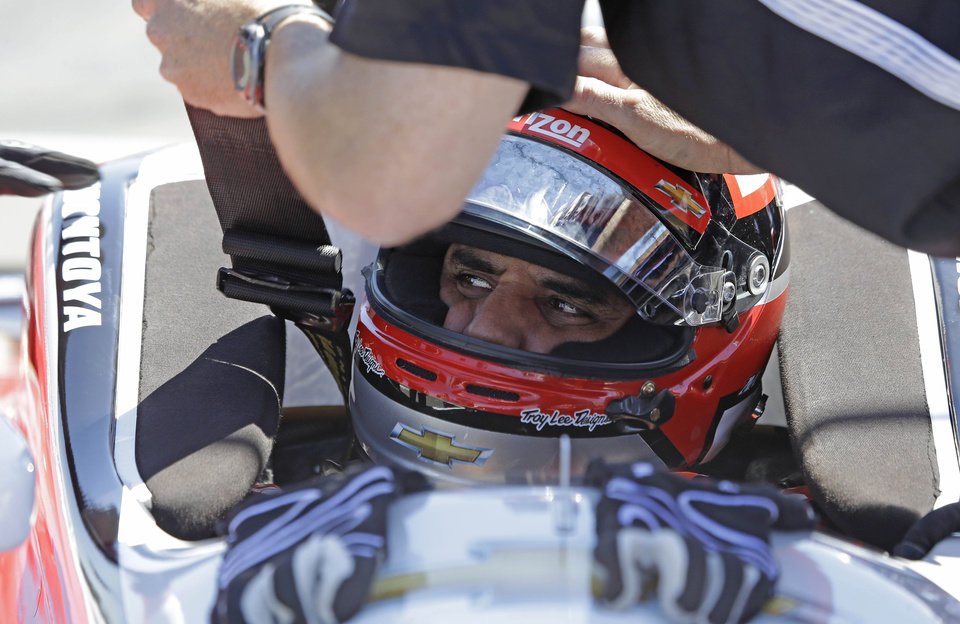 Photo - Juan Pablo Montoya, of Colombia, is readied in his car before practice for the IndyCar auto race Saturday, Aug. 23, 2014, in Sonoma, Calif. (AP Photo/Eric Risberg)