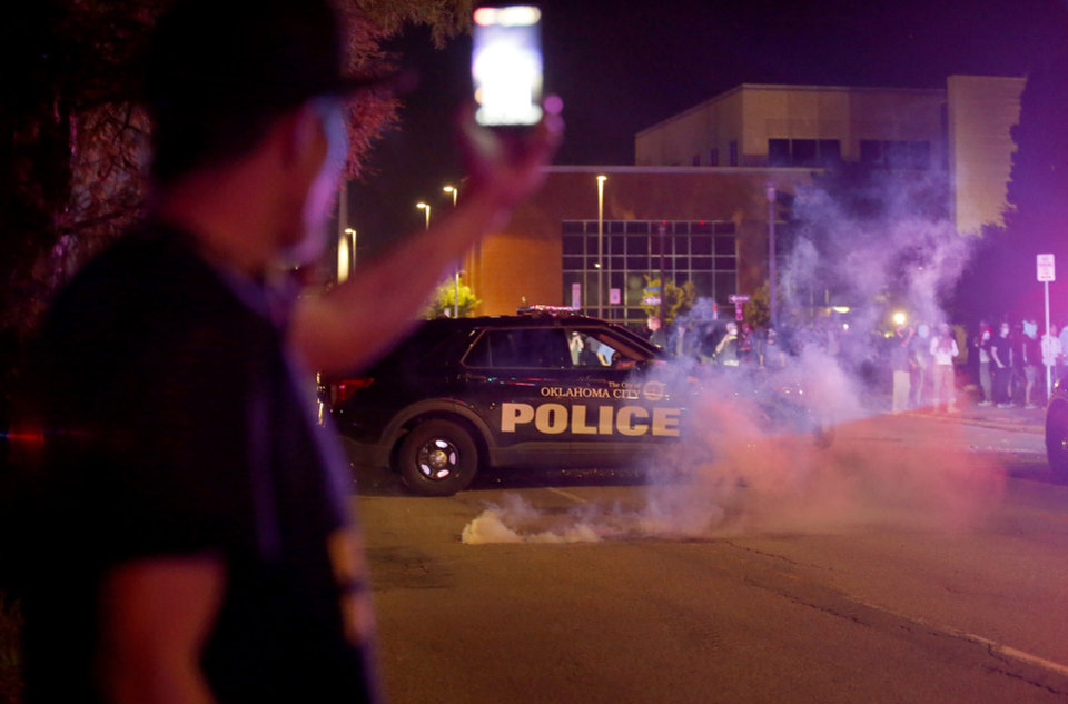Photo - Protesters films tear gas in front of the Oklahoma City Police Department in Oklahoma City, Saturday, May 30, 2020. The protest was in response to the death of George Floyd. [Sarah Phipps/The Oklahoman]