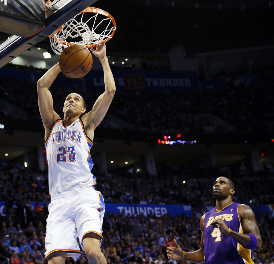 Photo - Oklahoma City's Kevin Martin (23) dunks the ball in front of Los Angeles' Antawn Jamison (4) during an NBA basketball game between the Oklahoma City Thunder and the Los Angeles Lakers at Chesapeake Energy Arena in Oklahoma City, Friday, Dec. 7, 2012. Photo by Nate Billings, The Oklahoman