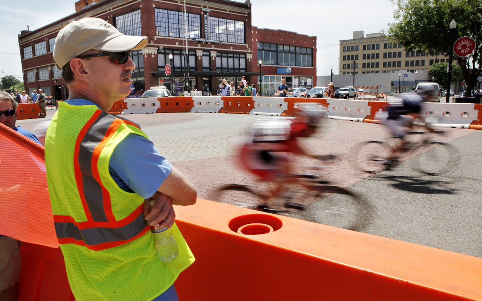 Photo - Cyclists speed past volunteer Lance Galvin during the Oklahoma City ProAm Classic, with races scheduled from 11 a.m. to 9 p.m. in Automobile Alley,  just north of downtown Oklahoma City on Saturday, June 2,  2012,  Galvin was among a group of Sandridge employees    who assisted along the course.  He was a crossing monitor on Broadway, helping pedestrians safely cross streets without interfering with the cyclists on the course. Photo by Jim Beckel, The Oklahoman