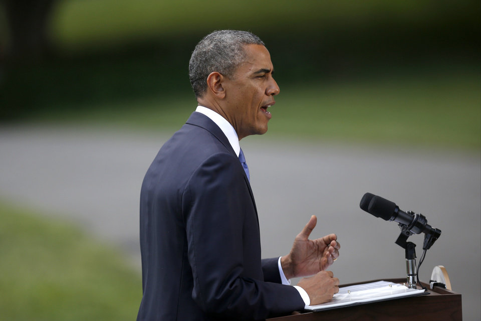 Photo - President Barack Obama talks about his administration's response to a growing insurgency foothold in Iraq, Friday, June 13, 2014, on the South Lawn of the White House in Washington, prior to boarding the Marine One Helicopter for Andrews Air Force Base, Md., then onto North Dakota and California. (AP Photo/Charles Dharapak)