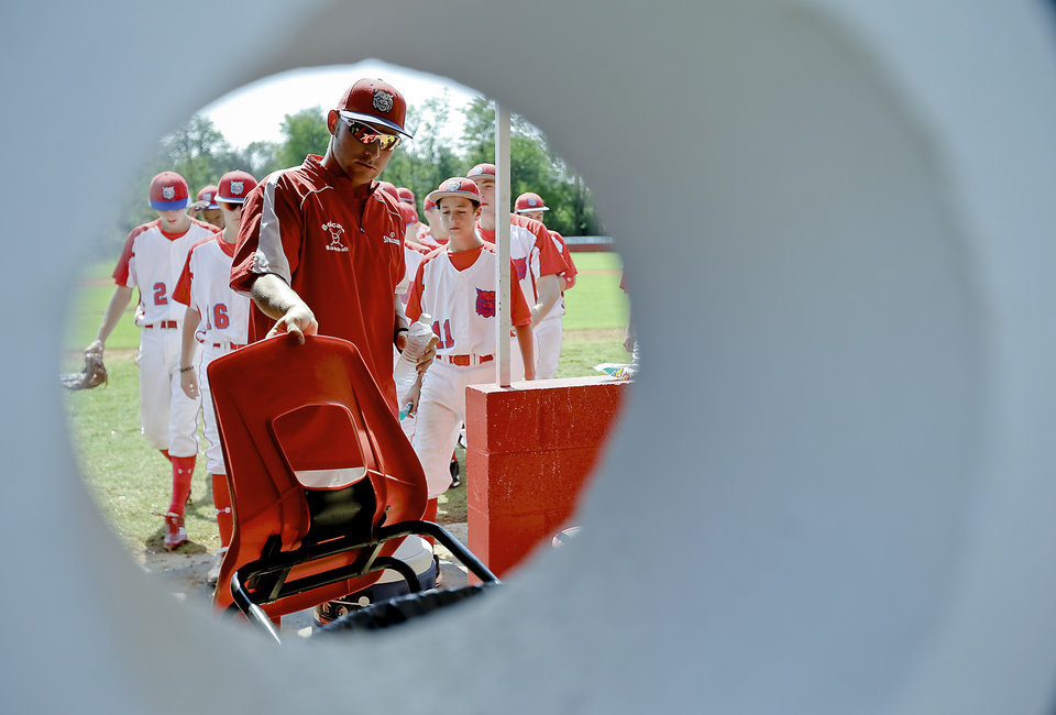 Photo - Former Major League Baseball player and current head coach of the Binger-Oney High School baseball team Reggie Willits takes his chair back to the dugout as the Bobcats play a game on Thursday, Sept. 20, 2012, in Binger, Okla. Photo by Chris Landsberger, The Oklahoman