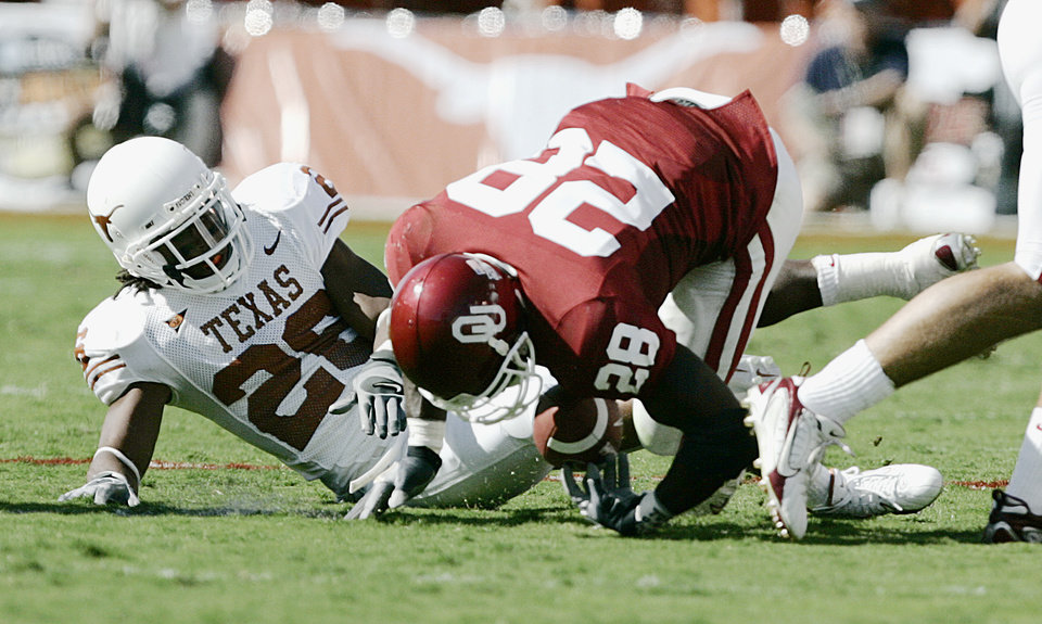 Photo - Oklahoma's Adrian Peterson (28) fumbles the ball away to Texas in the first half during the University of Oklahoma Sooners (OU) college football game against the University of Texas (UT), in the Red River Shootout at the Cotton Bowl, on Saturday, Oct. 7, 2006, in Dallas, Tex.     by Bryan Terry, The Oklahoman  ORG XMIT: KOD
