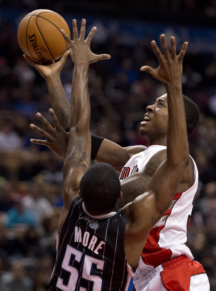 Toronto Raptors forward Ed Davis (right) drives to the hoop against Orlando Magic guard E'Twaun Moore (55) during first half NBA action in Toronto on Sunday, Nov. 18, 2012. (AP Photo\THE CANADIAN PRESS,Frank Gunn)